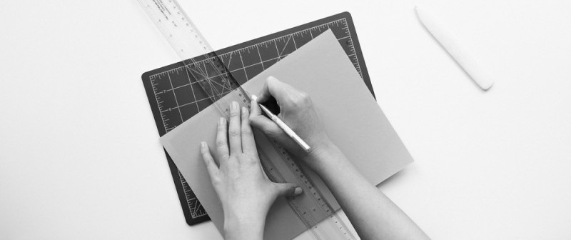 A person drawing a customization on a sheet of paper with a ruler